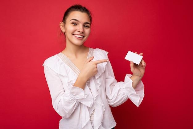 Foto van een mooie positief lachende jonge donkerblonde vrouw die een witte blouse draagt, geïsoleerd over rood