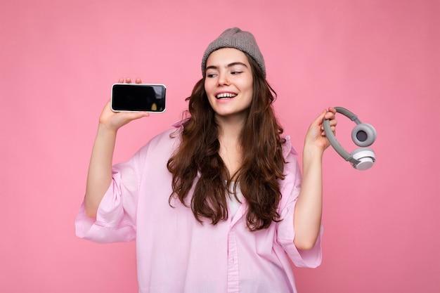Foto van een mooie positief lachende jonge vrouw die een stijlvolle, casual outfit draagt, geïsoleerd op kleurrijk