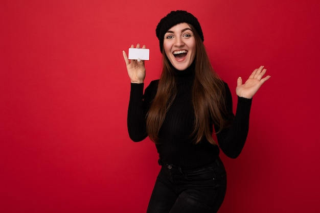 Foto van een mooie verbaasde jonge brunette vrouw met een zwarte trui en muts geïsoleerd op een rode achtergrond die een creditcard vasthoudt en naar de camera kijkt. kopieer ruimte