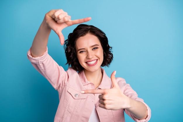 Foto van een mooie vrolijke dame die armen en handen vasthoudt en focuskader maakt