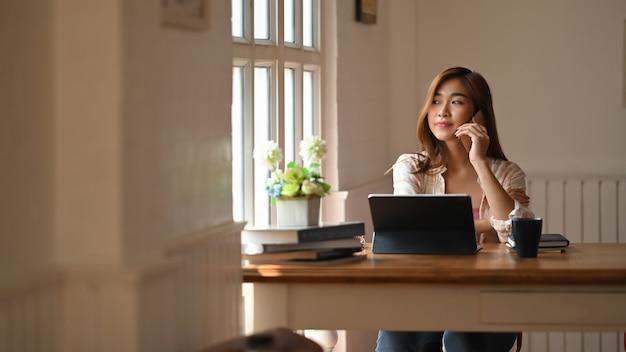 Foto van een mooie vrouw die een smartphone gebruikt om iemand te bellen terwijl ze vooraan zit een computertablet met toetsenbordbehuizing aan houten werktafel over comfortabele woonkamer