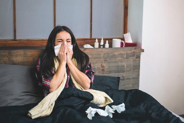 Foto van een mooie vrouw in het bed met zakdoek. ziek vrouwelijk model heeft loopneus. meisje maakt een remedie voor de verkoudheid