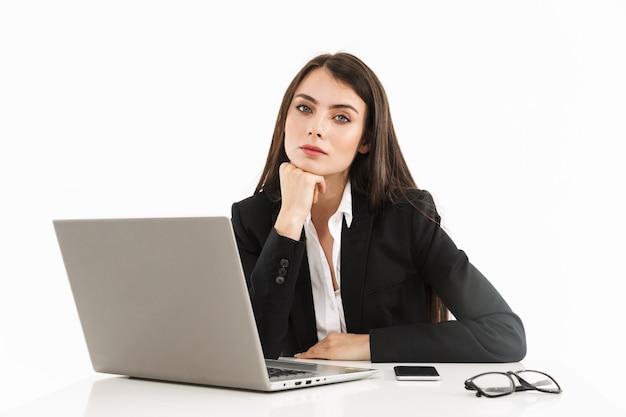 Foto van een mooie vrouwelijke werkneemster, gekleed in formele kleding, zittend aan een bureau en werkend op een laptop op kantoor geïsoleerd over een witte muur