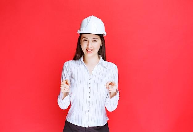 Foto van een mooie zakenvrouw die een veiligheidshoed draagt die wijst.