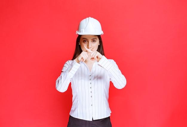 Foto van een mooie zakenvrouw die een veiligheidshoed draagt met gekruiste vingers.