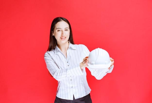 Foto van een mooie zakenvrouw die een veiligheidshoed op een rode muur houdt.