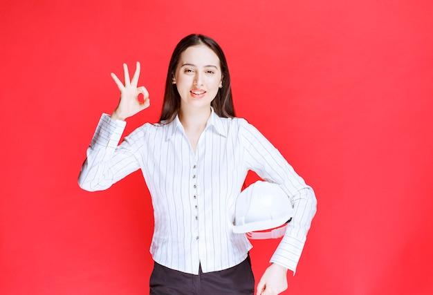 Foto van een mooie zakenvrouw die een veiligheidshoed vasthoudt en een goed gebaar toont.