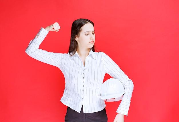 Foto van een mooie zakenvrouw die een veiligheidshoed vasthoudt en spieren toont.