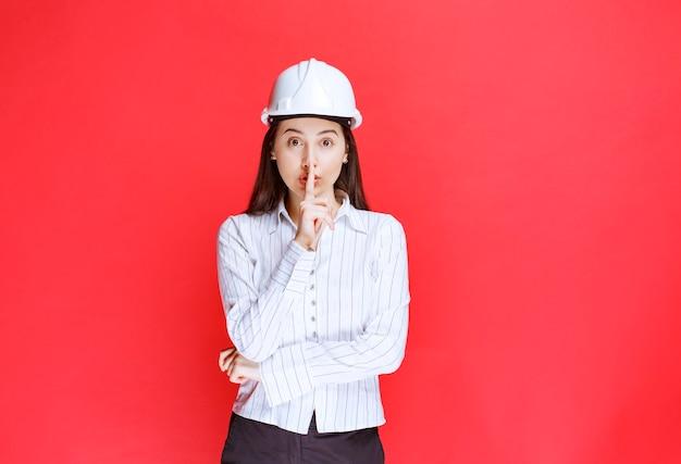 Foto van een mooie zakenvrouw met een veiligheidshoed die een stil teken doet.