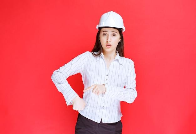 Foto van een mooie zakenvrouw met een veiligheidshoed die met de vingers naar beneden wijst.