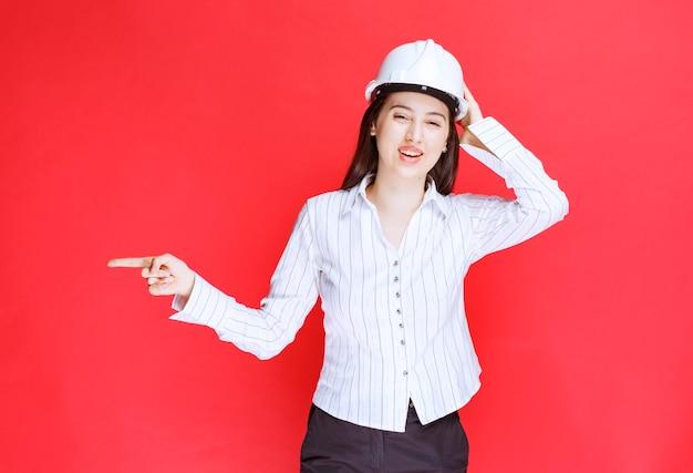 Foto van een mooie zakenvrouw met een veiligheidshoed die met de vingers wegwijst.