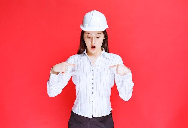 Foto van een mooie zakenvrouw met een veiligheidshoed die naar zichzelf wijst.