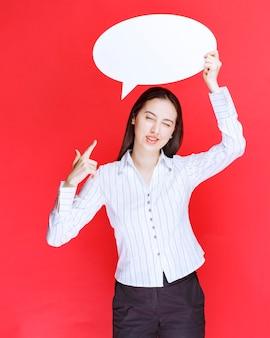 Foto van een mooie zakenvrouw wijzend op een lege tekstballon.