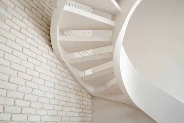 Foto van een muur van witte baksteen en een wenteltrap in het huis