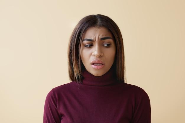 Foto van een ongelukkig gefrustreerd aantrekkelijke jonge vrouw van gemengd ras in stijlvolle kleding die zich perplexe gezichtsuitdrukking heeft bezorgd, naar beneden kijkt en de mond opent, besluiteloos iets zegt.