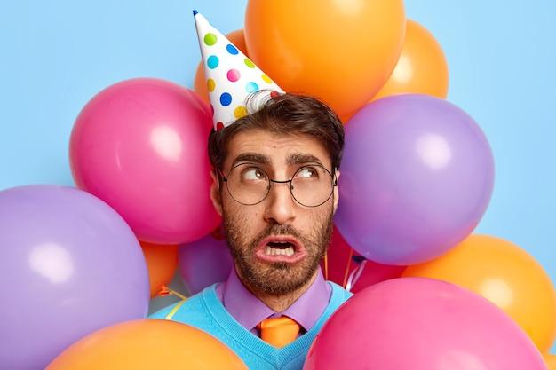 Foto van een ongelukkige man omringd door partij ballonnen poseren