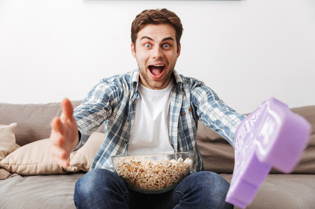 Foto van een ongeschoren man die alleen thuis rust en naar spel kijkt, met grote speelgoedhandschoen en popcorn
