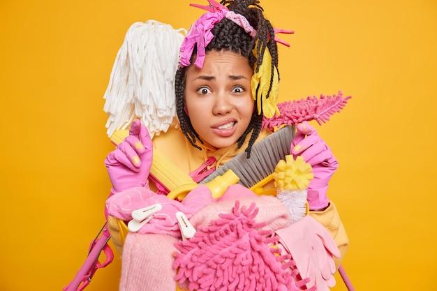 Foto van een ontstemde vrouw met een donkere huid grijnst met een grijns en een verbaasde blik wil niet opruimen