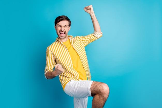 Foto van een opgetogen man die zijn vuisten opheft om het nationale voetbalteam te vieren, het spel te winnen, schreeuw ja, draag goed uitziende gemoedskleding geïsoleerd op een blauwe achtergrond