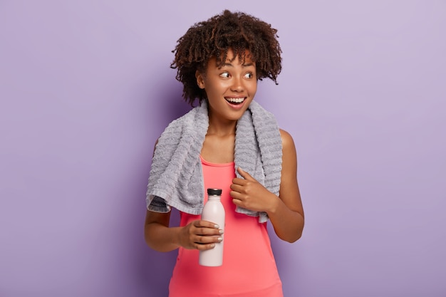 Foto van een opgetogen sportvrouw met een donkere huidskleur heeft een afro-kapsel, kijkt opzij met een glimlach, gekleed in een roze top, draagt een fles, drinkt water terwijl ze dorst heeft tijdens de training, oefeningen binnenshuis.