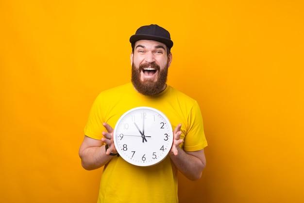 Foto van een opgewonden man met een klok in de buurt van een gele muur glimlachend