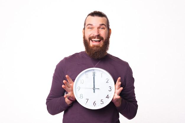Foto van een opgewonden man met een klok lacht