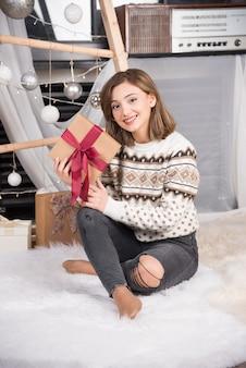 Foto van een opgewonden vrouw die op het tapijt zit en een kerstcadeau vasthoudt