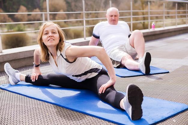 Foto van een ouder stel dat zich buiten op gymnastiekmatten uitrekt