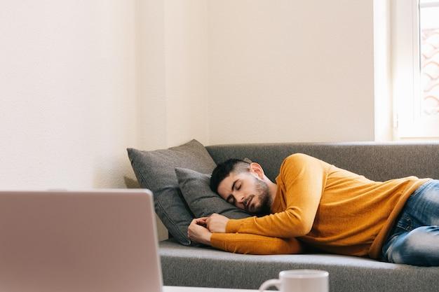 Foto van een overwerkte jonge volwassen man die thuis ontspannen op de bank slaapt. dutje terwijl je uitrust thuiswerken, spaanse gewoonte.