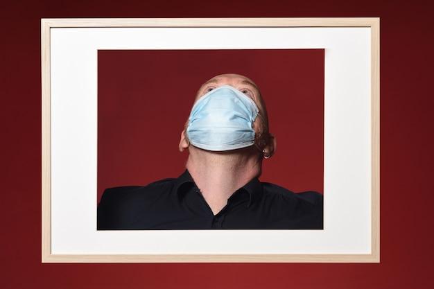 Foto van een portret van een man met masker opzoeken op een rode achtergrond