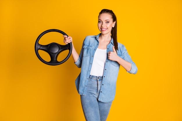 Foto van een positief meisje dat het stuur vasthoudt, een nieuw autoproduct aanraadt, een spijkerbroek draagt, geïsoleerd over een heldere glanskleurachtergrond