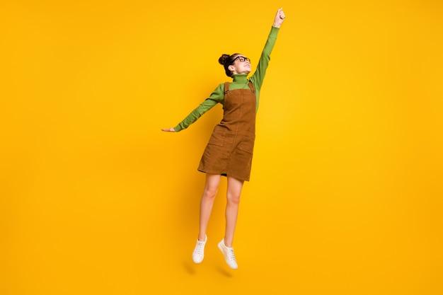 Foto van een positief meisje dat springt en een groene trui draagt, een rok over het algemeen geïsoleerd over een gele achtergrond