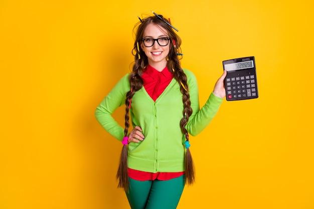 Foto van een positief meisje met een potloodkapsel, een rekenmachine, een shirtbroek, een geïsoleerde felle kleurachtergrond