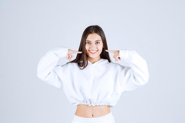 Foto van een positief schattig jong meisjesmodel dat op haar wangen wijst.