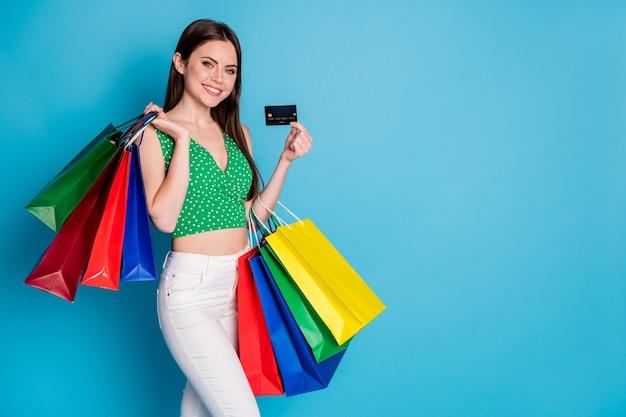 Foto van een positief vrolijk meisje dat veel tassen vasthoudt, geniet van het betalen van een creditcard, draag een witte broek, een broek singlet geïsoleerd op een blauwe achtergrond