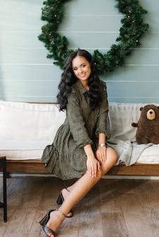 Foto van een positieve dame zittend op een gezellige bank in een huis binnenshuis met kerst