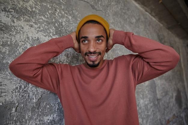 Foto van een positieve jonge donkere man met bruine ogen die zijn oren bedekken met opgeheven handpalmen en vrolijk lacht terwijl hij opzij keek
