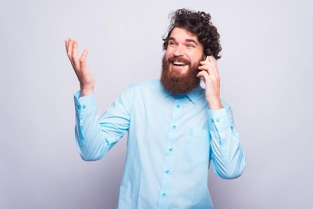 Foto van een positieve jonge man praten met zijn telefoon in de buurt van grijze muur