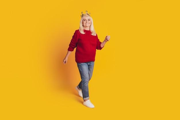 Foto van een positieve oude vrouw met een gouden kroon gaat op een gele achtergrond