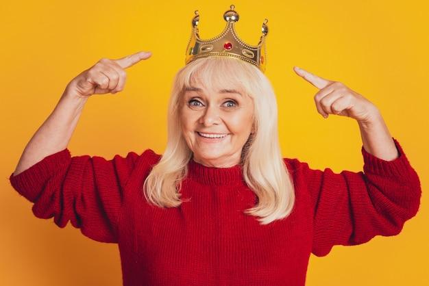 Foto van een positieve oude vrouw met een gouden kroon met puntvinger