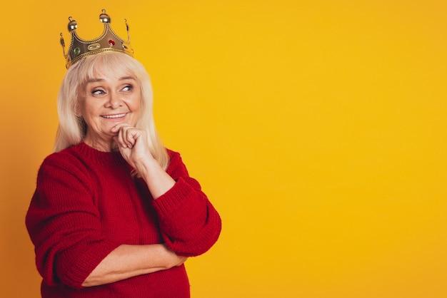 Foto van een positieve oude vrouw met een gouden kroon ziet er lege ruimte uit denk
