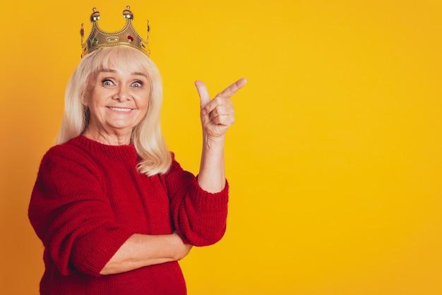 Foto van een positieve oude vrouw met een lege ruimte in de wijsvinger van het gouden kroonpunt