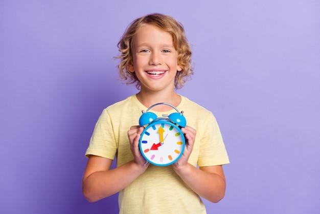 Foto van een positieve, vrolijke kleine jongen die de tijd van de klok vasthoudt, geïsoleerd over een violette kleurachtergrond