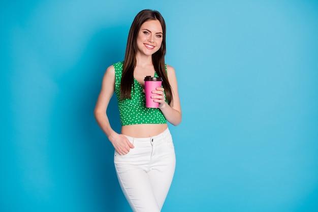 Foto van een positieve, vrolijke, schattige meid die koffie houdt, geniet van vrije tijd, draag mooie kleding die is geïsoleerd op een blauwe achtergrond