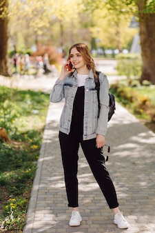 Foto van een positieve vrolijke tienermeisje brengt tijd door in het park en het gebruik van mobiele telefoon.