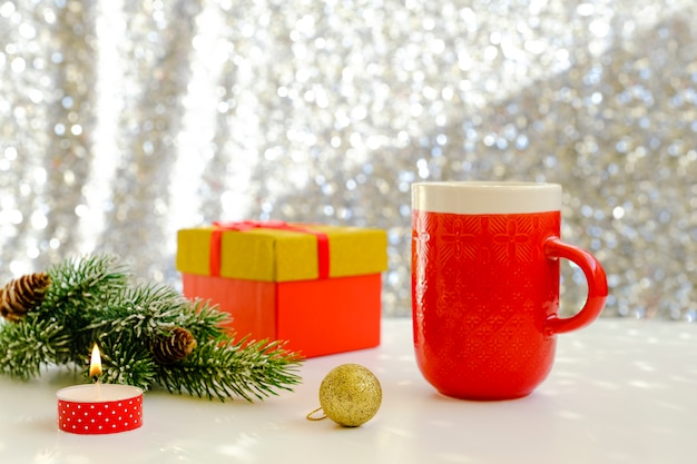 Foto van een prachtige kersttafel instelling, glanzende witte achtergrond met een rode koffiekopje, vuren tak.