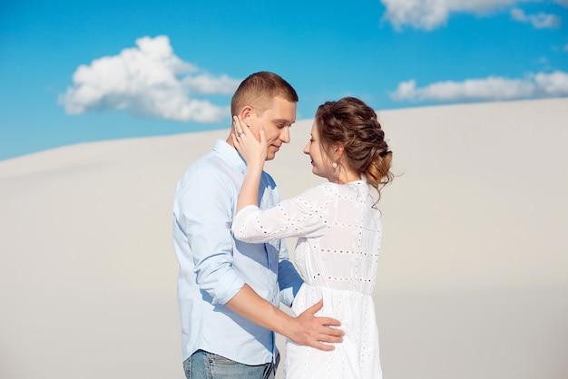 Foto van een prachtige paar man en vrouw glimlachend en knuffelen op een zanderige heuvel