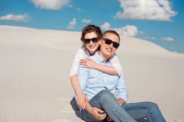 Foto van een prachtige paar man en vrouw glimlachend en knuffelen op een zandheuvel.