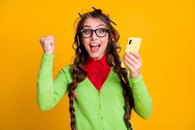 Foto van een rommelig kapsel van een gek meisje, met vuisten omhoog houden mobiele telefoon geïsoleerd op gele achtergrond