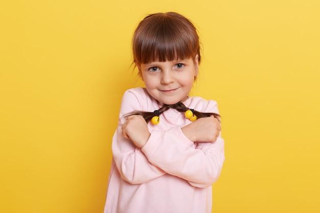 Foto van een schattig klein meisje dat zichzelf knuffelt, vlechtjes in handen houdt, lichtroze shirt draagt dat over een turkoois gele muur wordt geïsoleerd, verlegen kind dat liefde uitdrukt, ziet er goed uit.